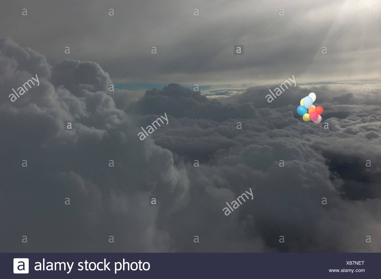 Bunch of multi-colored balloons flying in the sky above the clouds - Stock Image