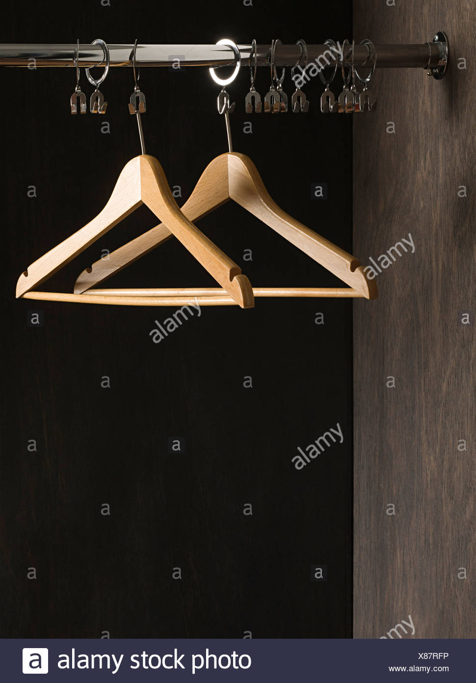 Clothes hangers in closet - Stock Image