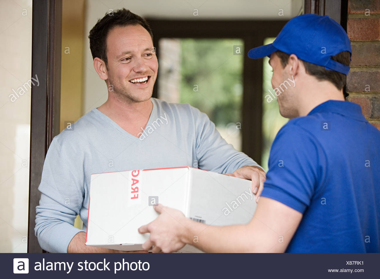 Man having a parcel delivered - Stock Image
