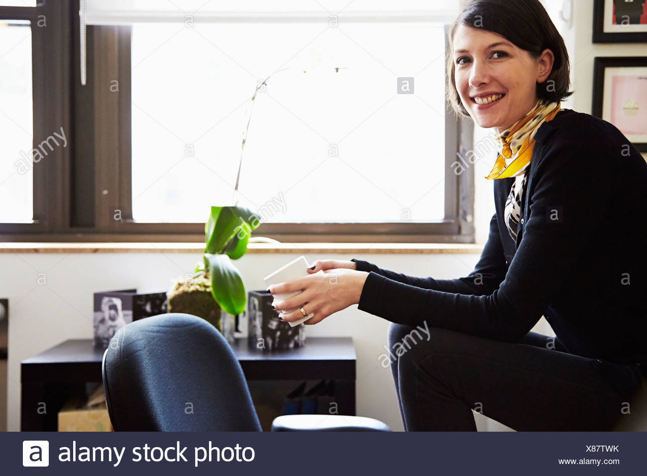 Businesswoman sitting in office - Stock Image