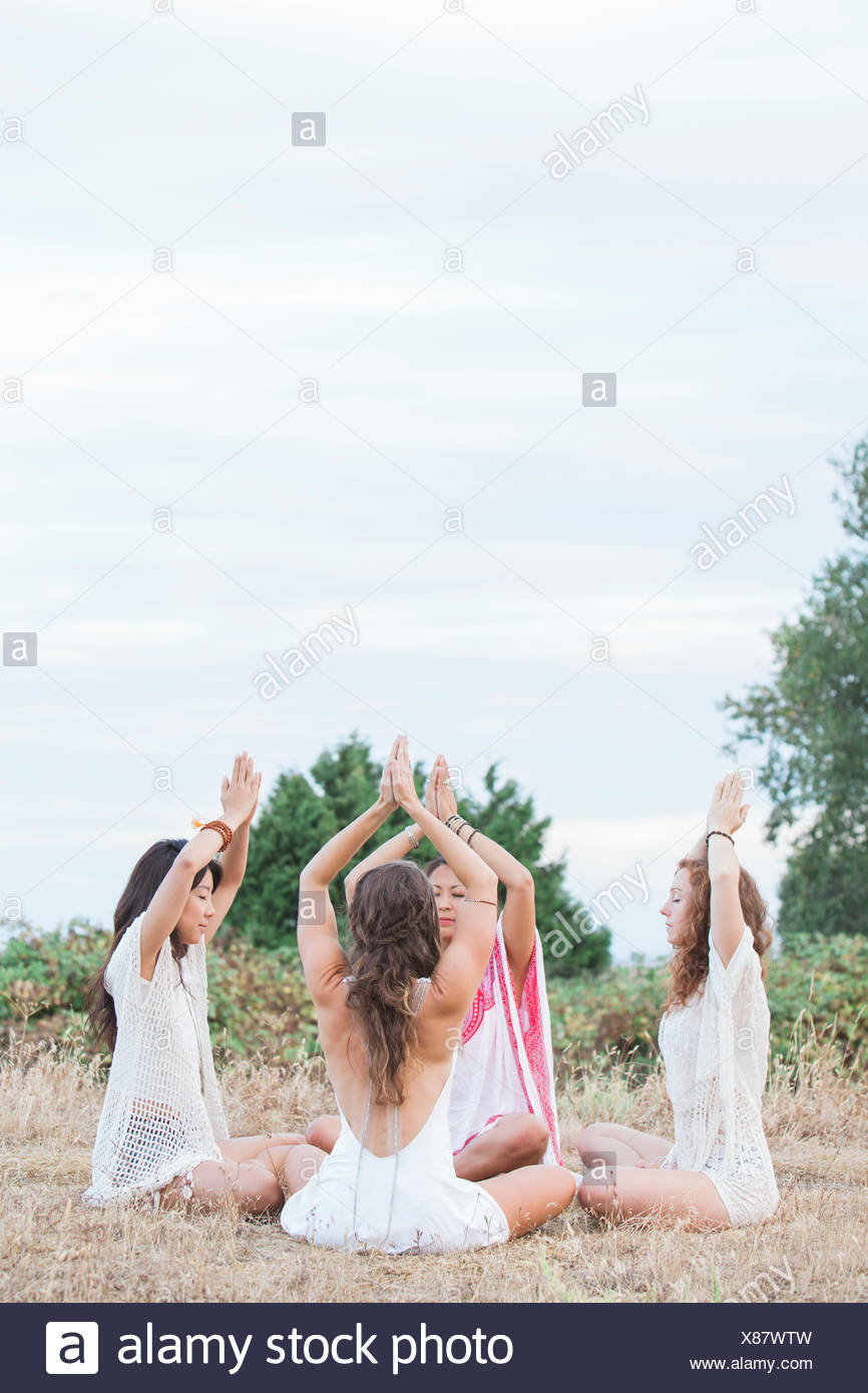 Boho women meditating with hands clasped overhead in circle in rural field - Stock Image