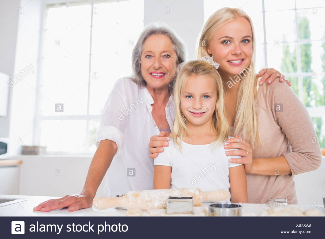 Cheerful mothers and daughters cooking together - Stock Image