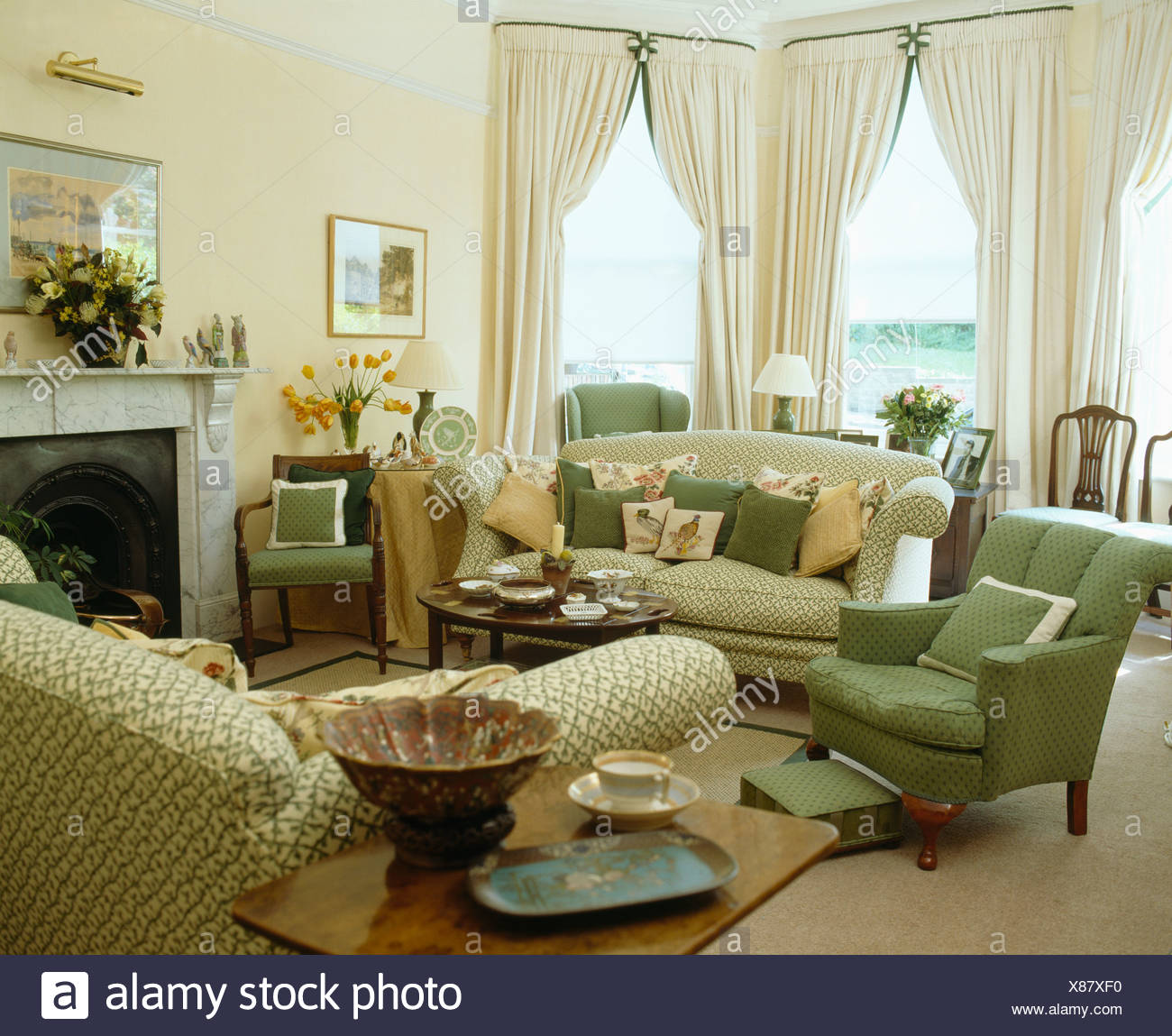 Green armchair and sofa piled with cushions in traditional ...