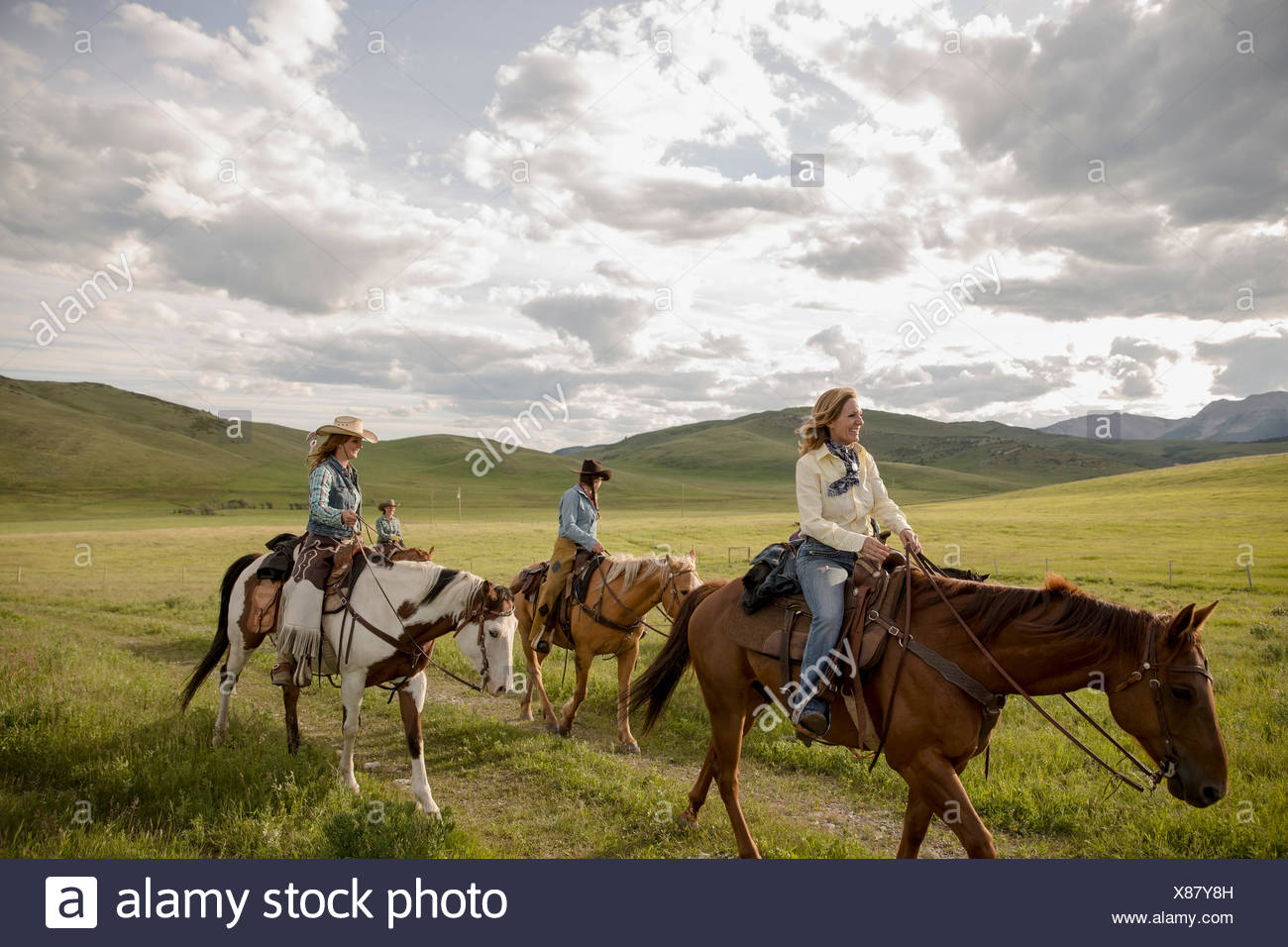Female ranchers horseback riding in remote field - Stock Image