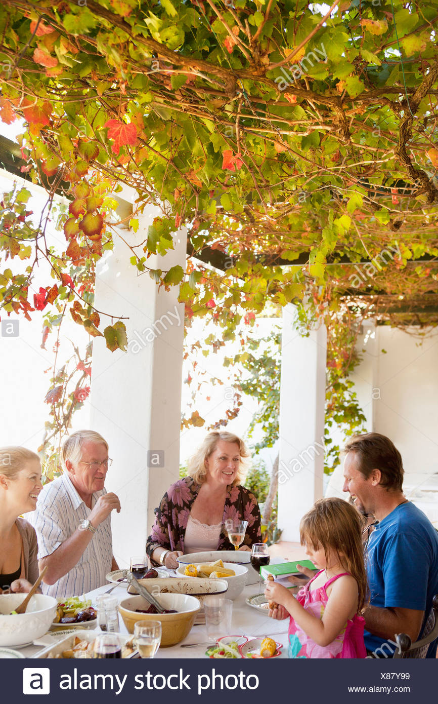 Family eating at table outdoors - Stock Image