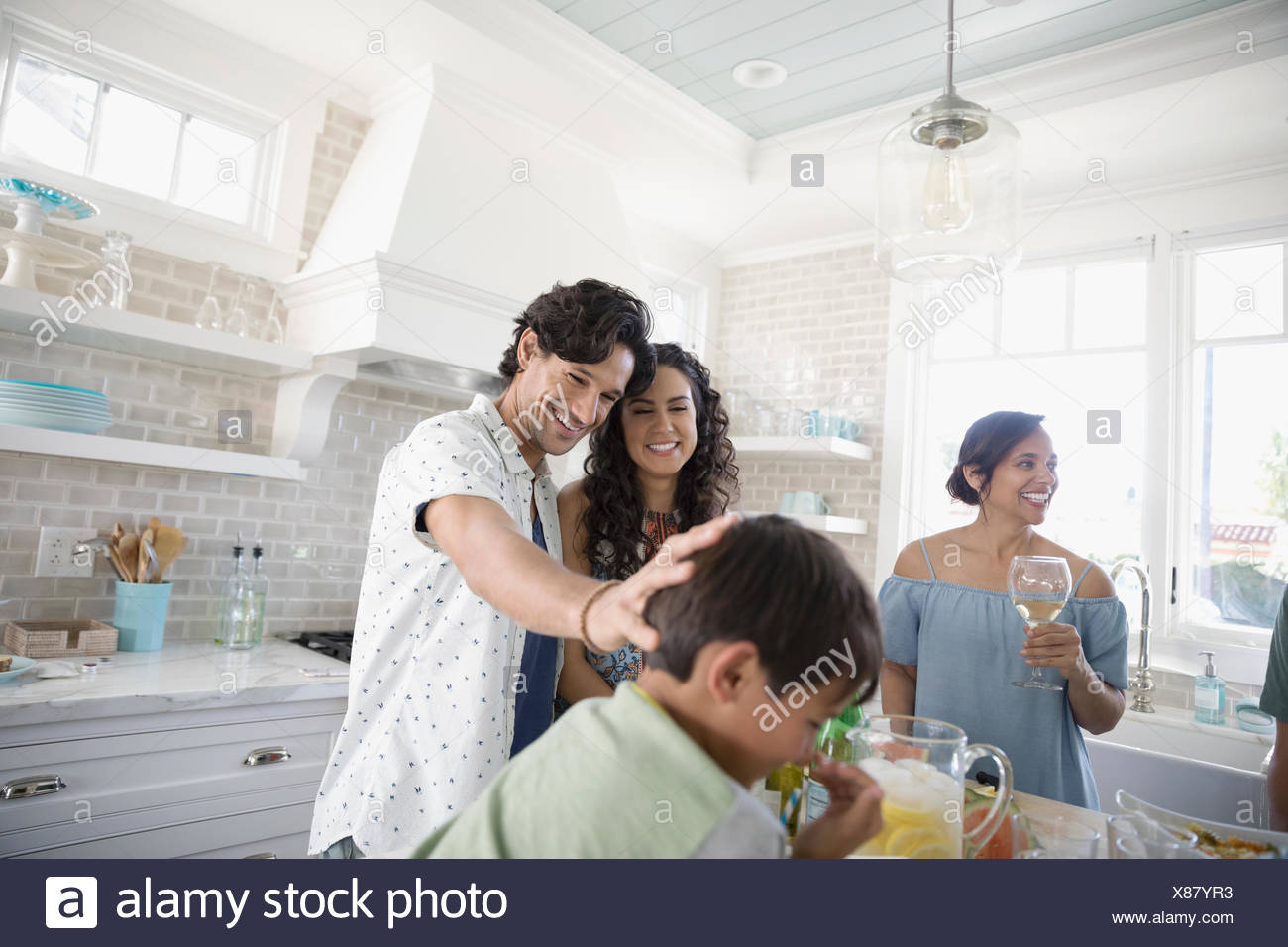Family eating and drinking in beach house kitchen - Stock Image