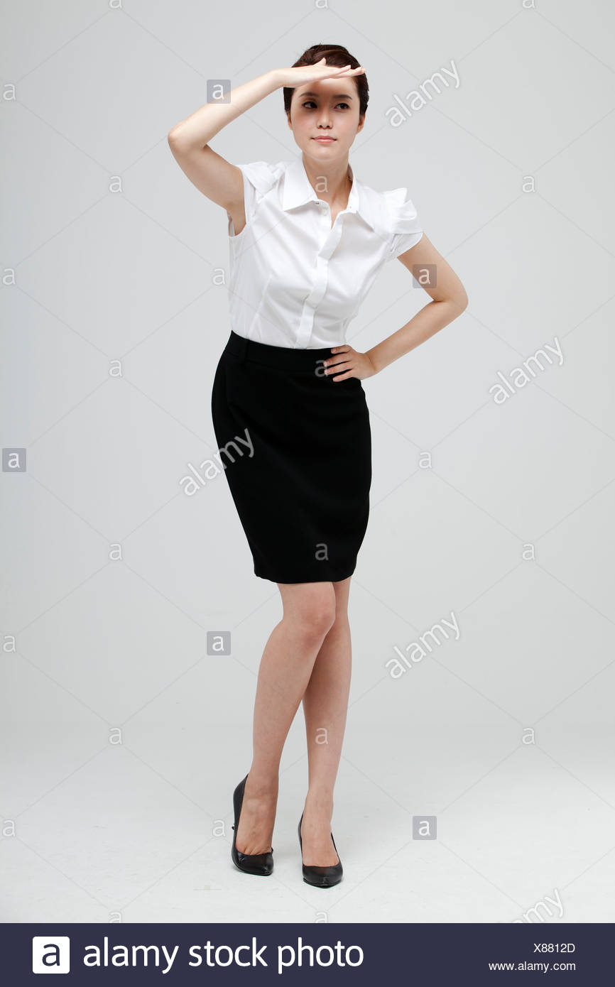 Asian Businesswoman Looking Upwards And Shielding Eye - Stock Image