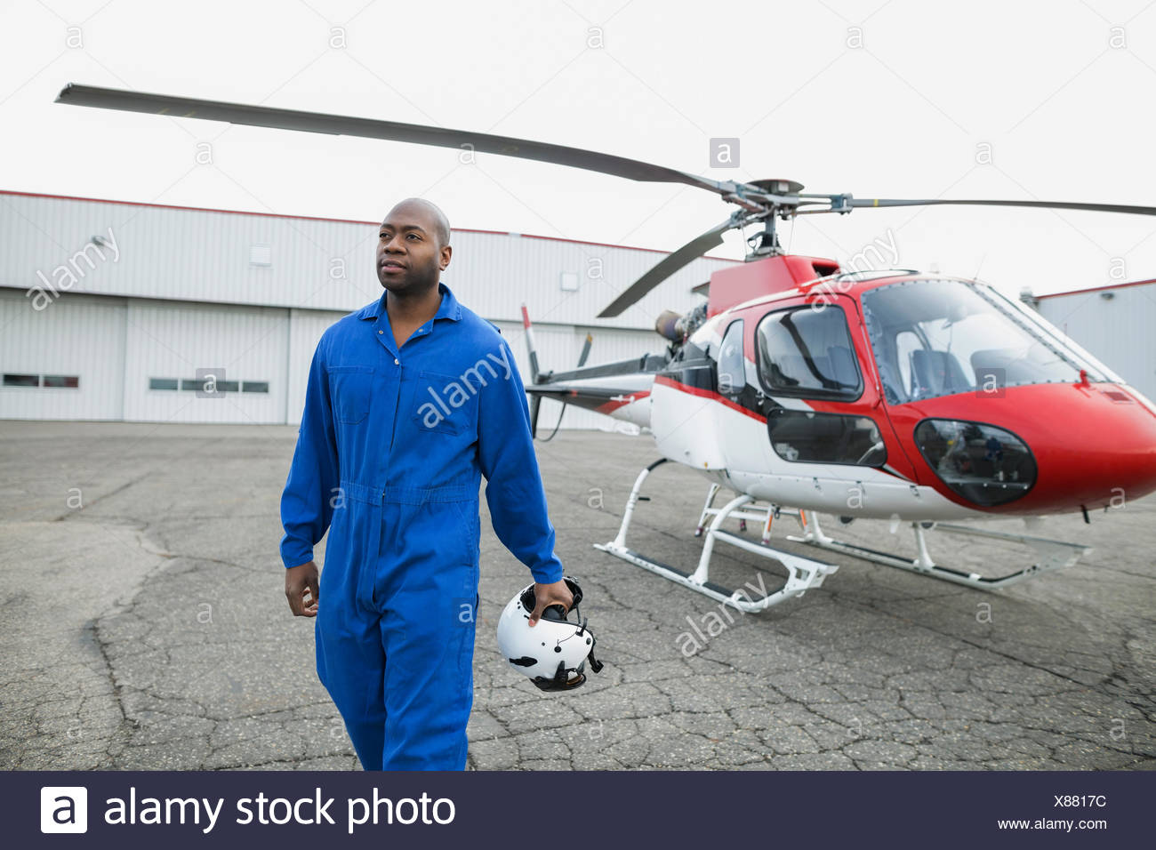 Pilot in coveralls walking away from helicopter - Stock Image
