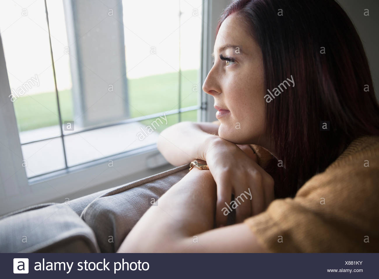 Pensive woman on sofa looking out window - Stock Image