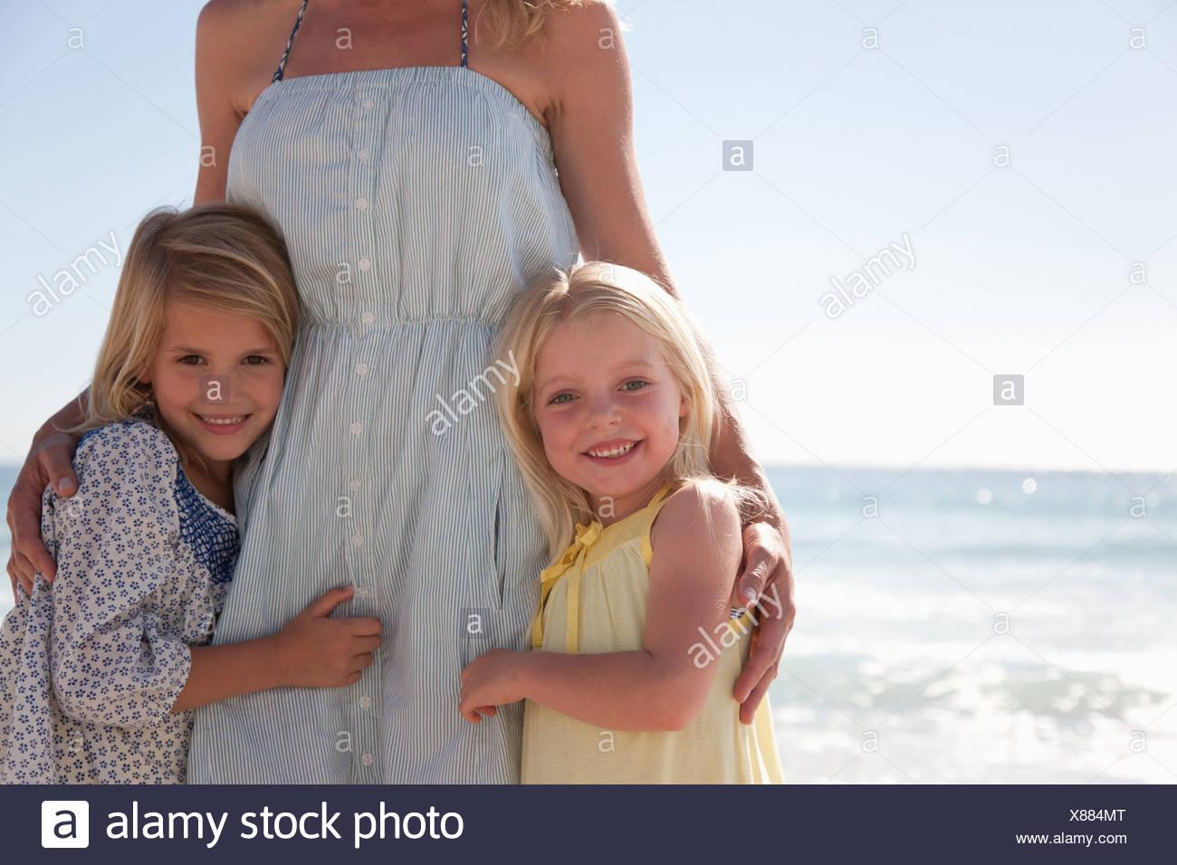 Girls hugging mother on beach - Stock Image
