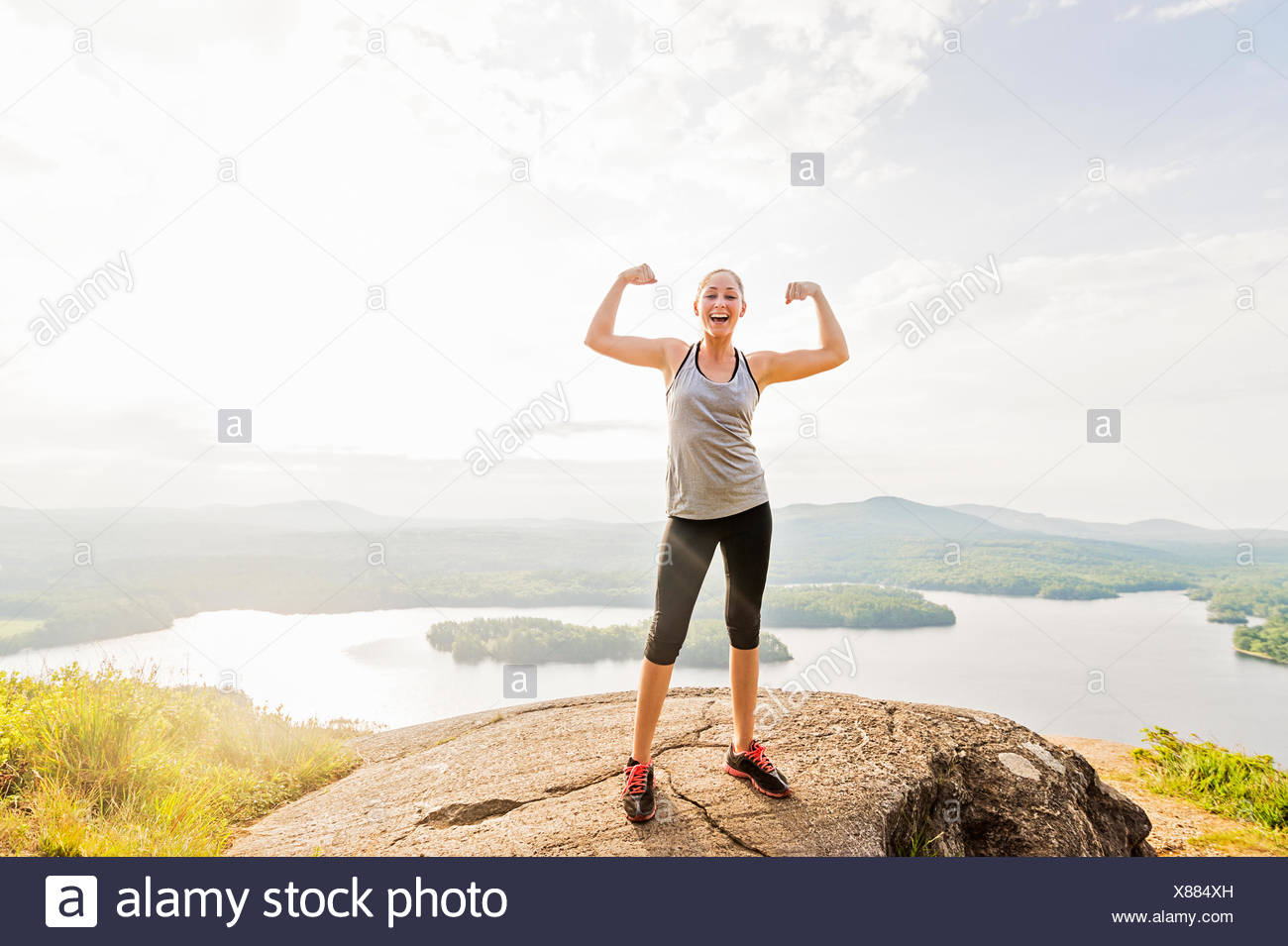 Young woman standing on top of mountain and flexing muscles - Stock Image