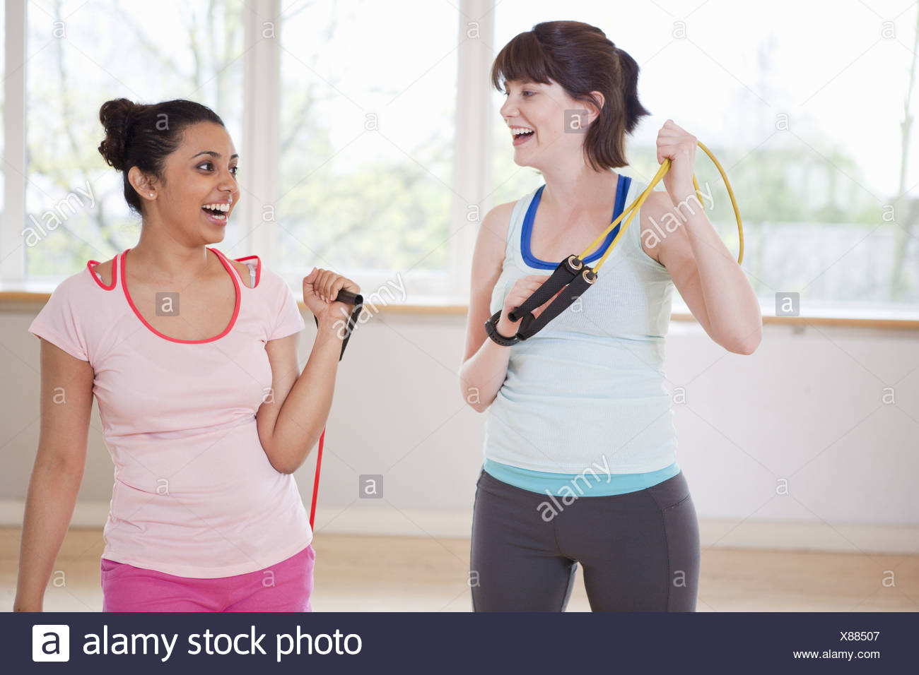 Women carrying resistance band in gym - Stock Image