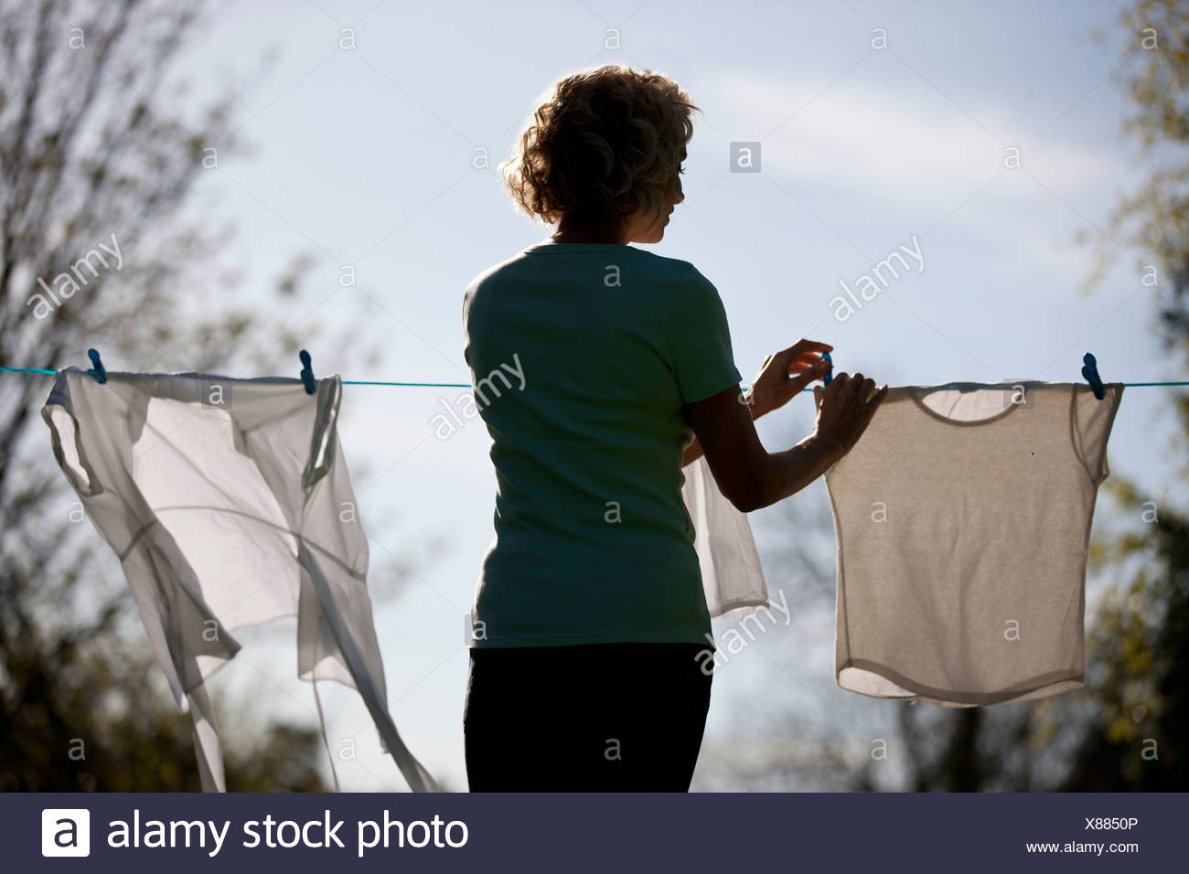 A mature woman pegging out washing on a washing line, rear view - Stock Image
