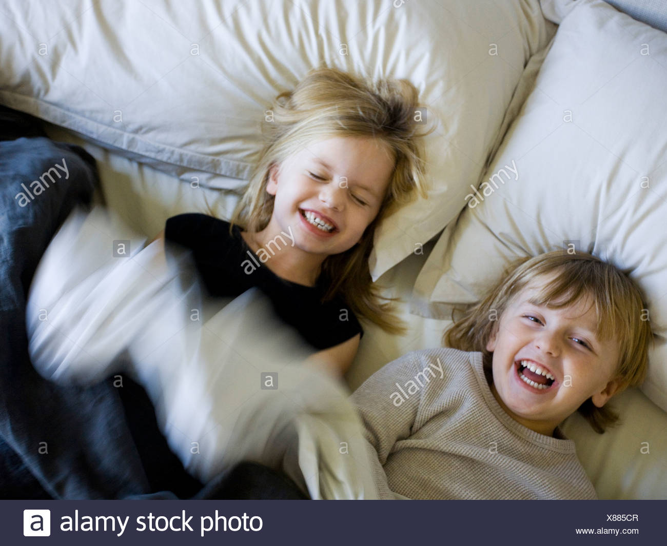 USA, Utah, Provo, Brother and sister (2-5) playing in bed - Stock Image