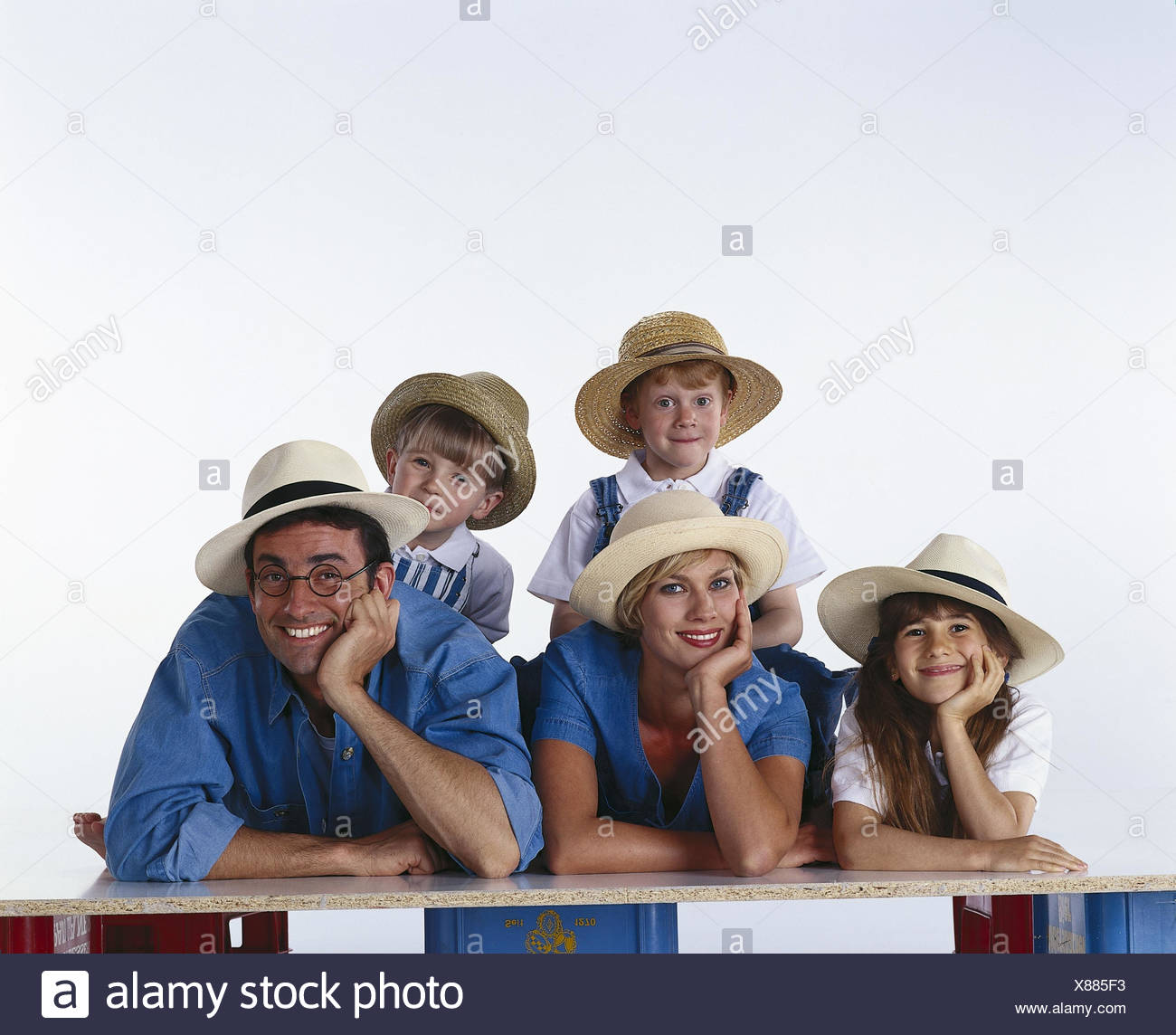 Family, hats, happy, hand, head, rest on, there, smile, group picture parents, woman, man, children, boys, girls, three, care, straw hat, headgear, positively, mood, happy, together, family picture, studio Stock Photo