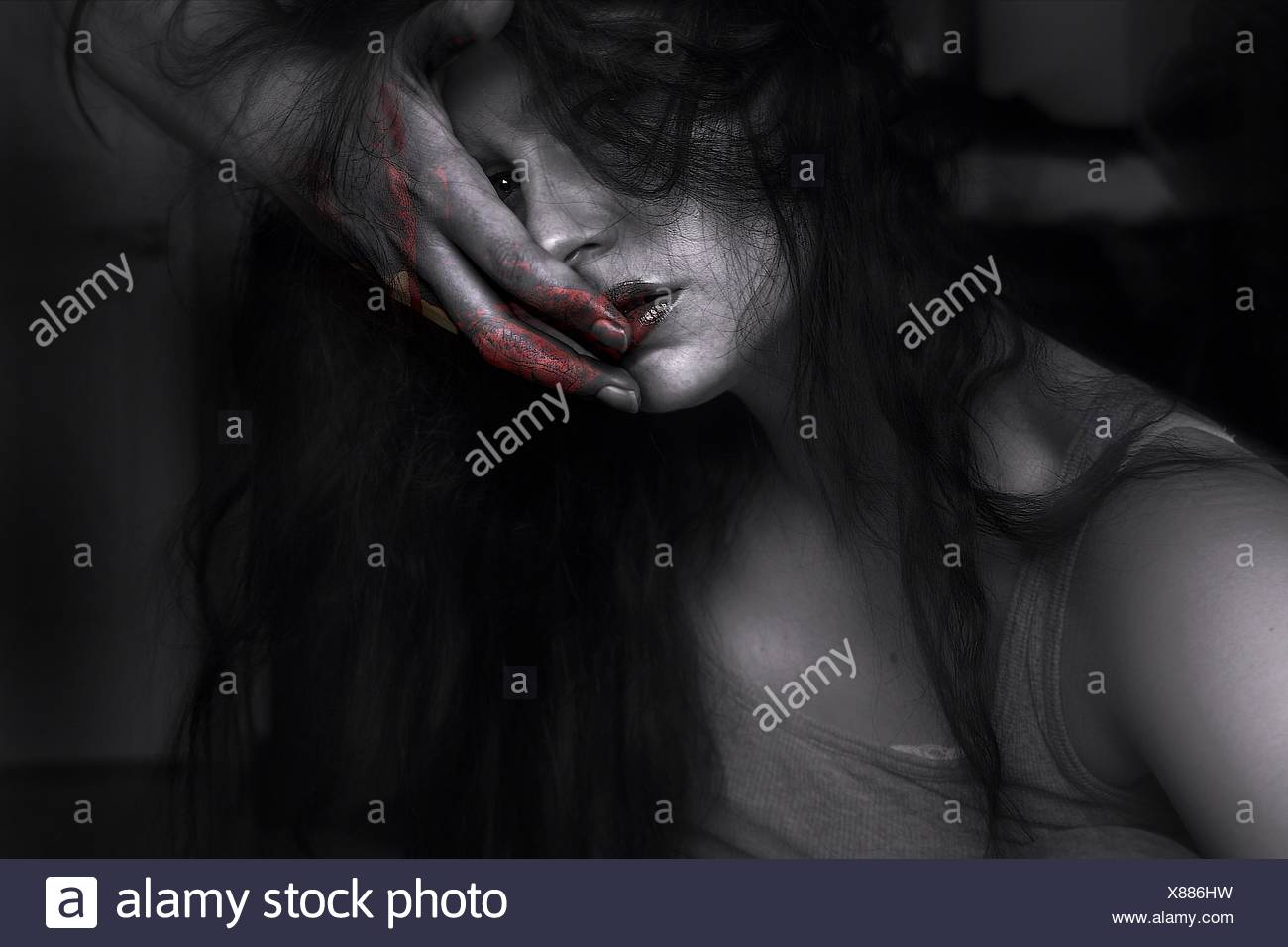 Portrait Of Woman With Red Paint On Hand Touching Face - Stock Image