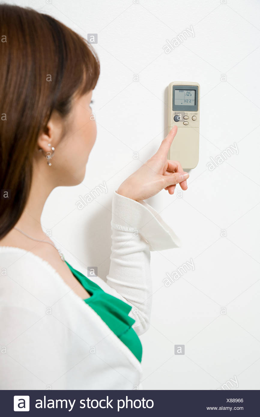 Woman pointing to thermostat Stock Photo