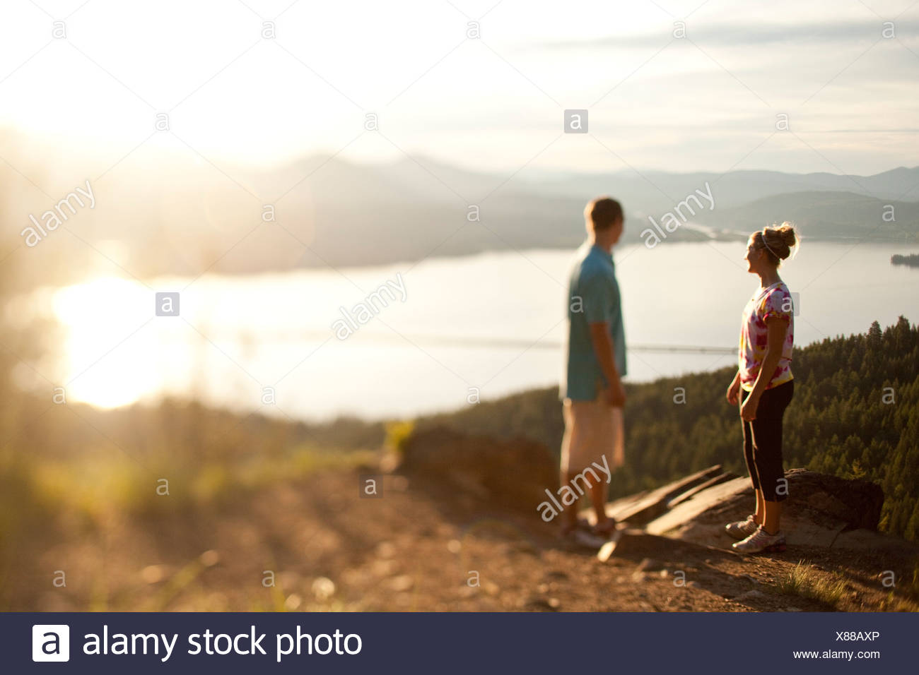 Two young adults talk at the edge of a cliff enjoying the view of the lake. - Stock Image