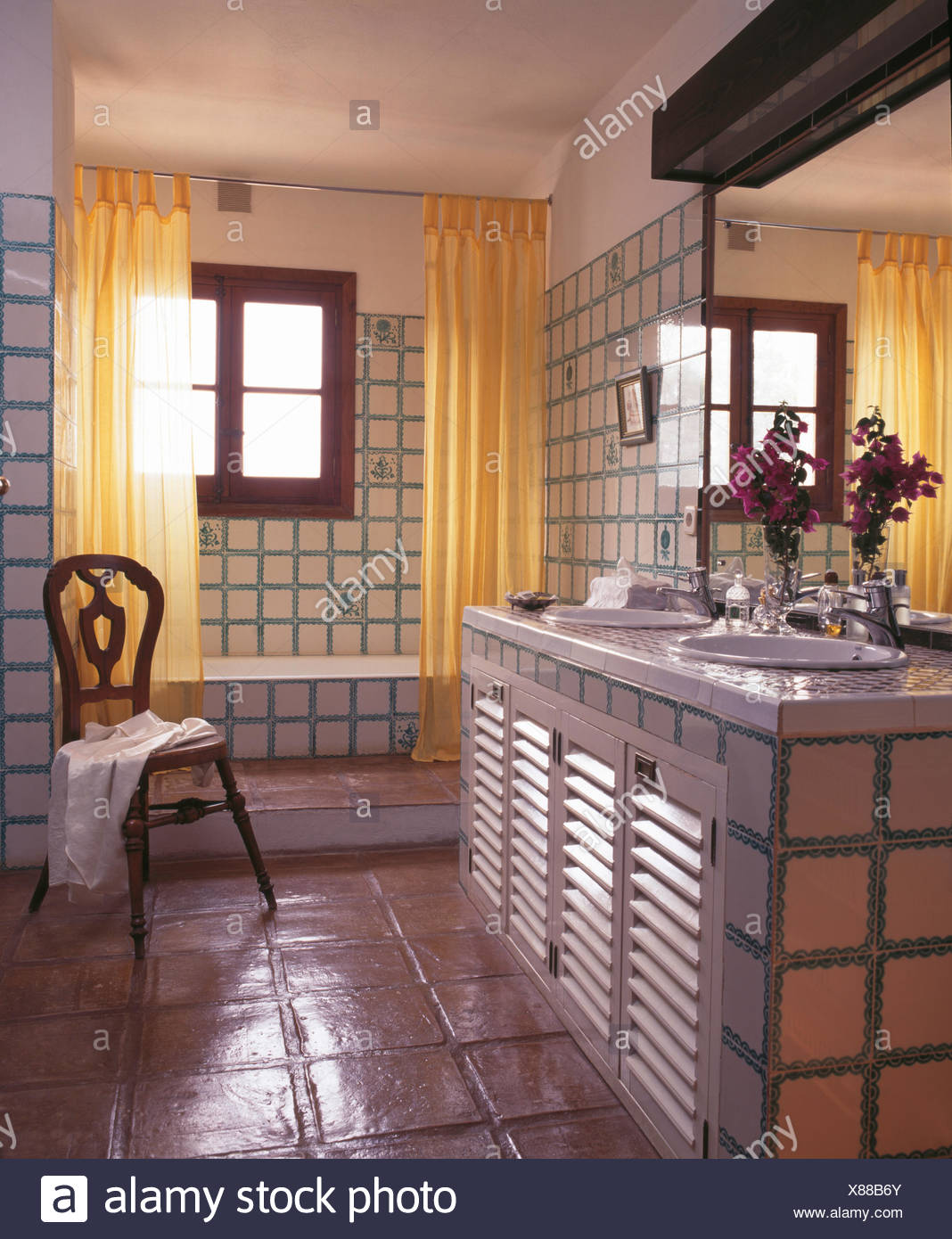 Yellow Shower Curtains On Bath In Tiled Spanish Country Bathroom With A Terracotta Floor