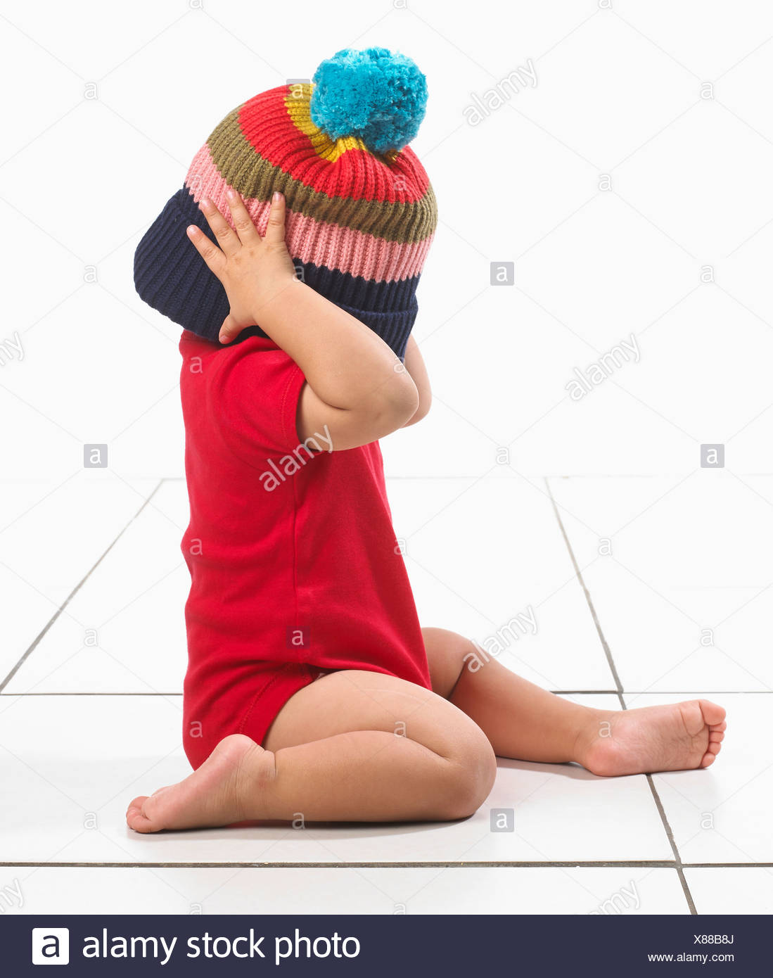 51e3b8fcc Baby boy (16 months) with colourful stripes woolly hat over head and ...