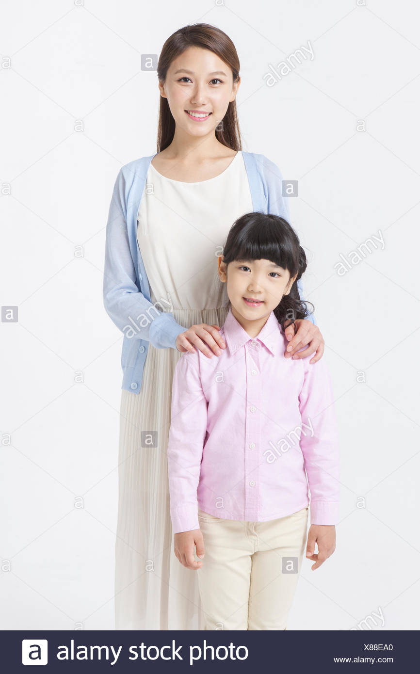 Mother standing behind her daughter with her hands on daughter's shoulder both staring forward with a smile - Stock Image