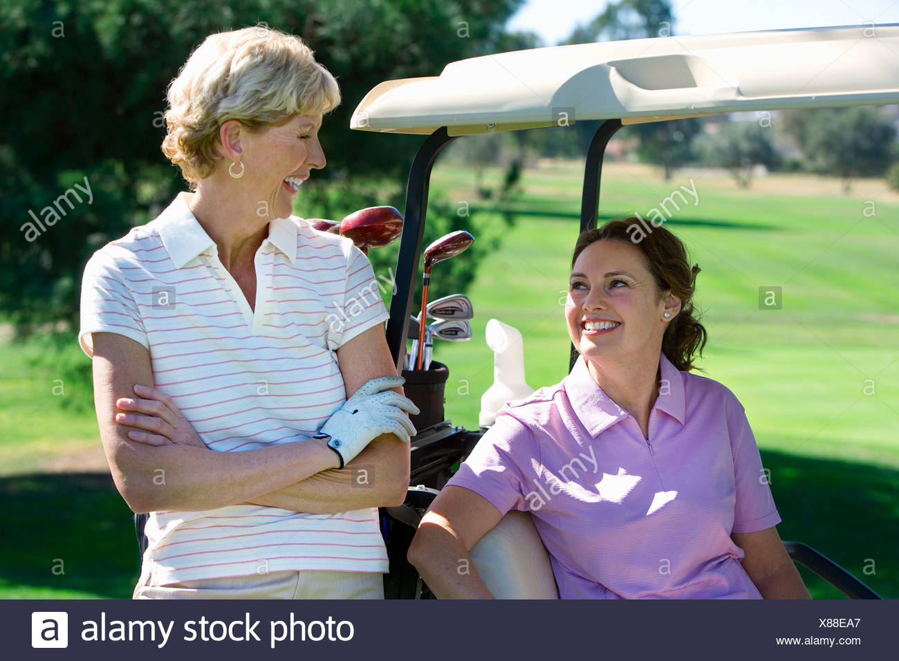 Two mature women talking on golf course, brunette sitting in golf buggy, blonde standing beside her, smiling - Stock Image
