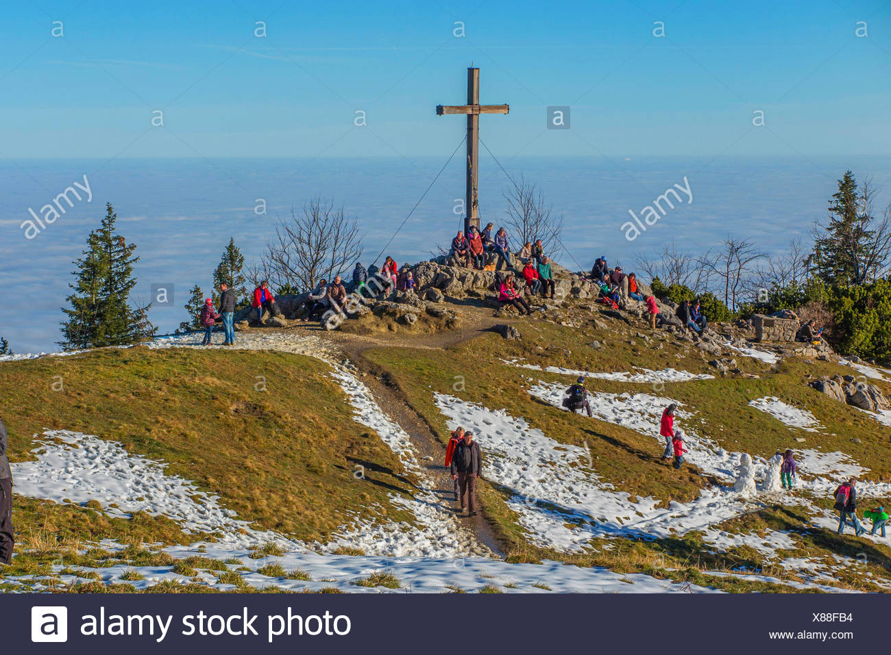 cross on the mountain summit in sunshine and mist in the valley, Germany, Bavaria, Kampenwand, Hohenaschau - Stock Image