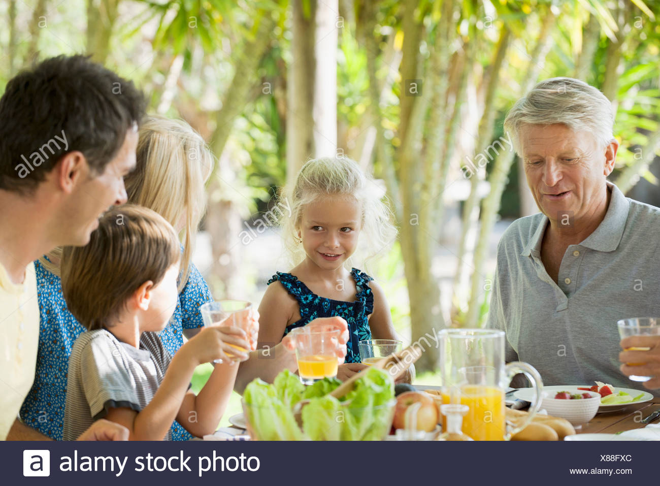 Multi-generation family having breakfast outdoors Stock Photo