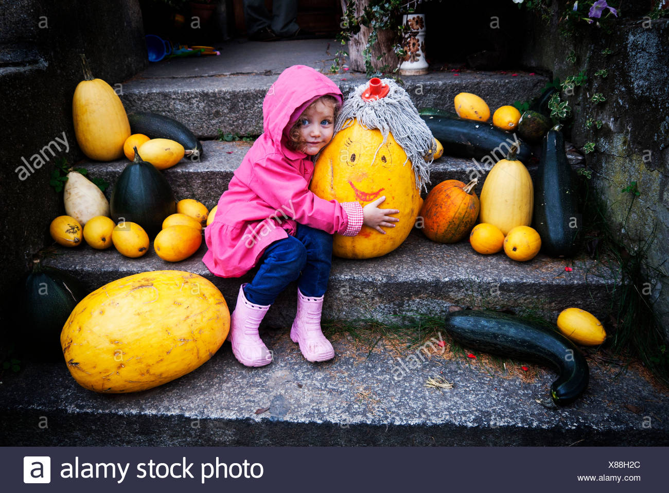 Girl (4-5) embracing pumpkin with mop on its head - Stock Image