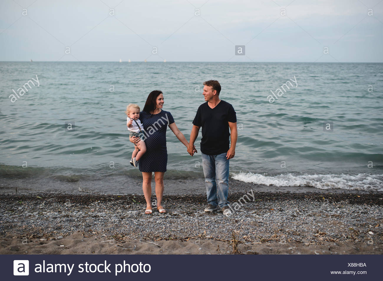 Pregnant couple at water's edge on beach with male toddler son, Lake Ontario, Canada - Stock Image