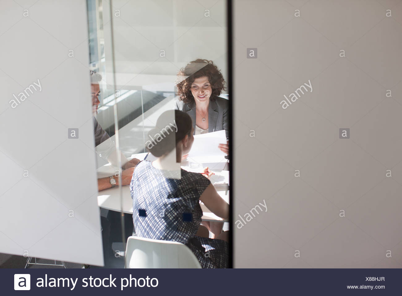 Businessman and businesswoman reviewing paperwork in sunny office - Stock Image