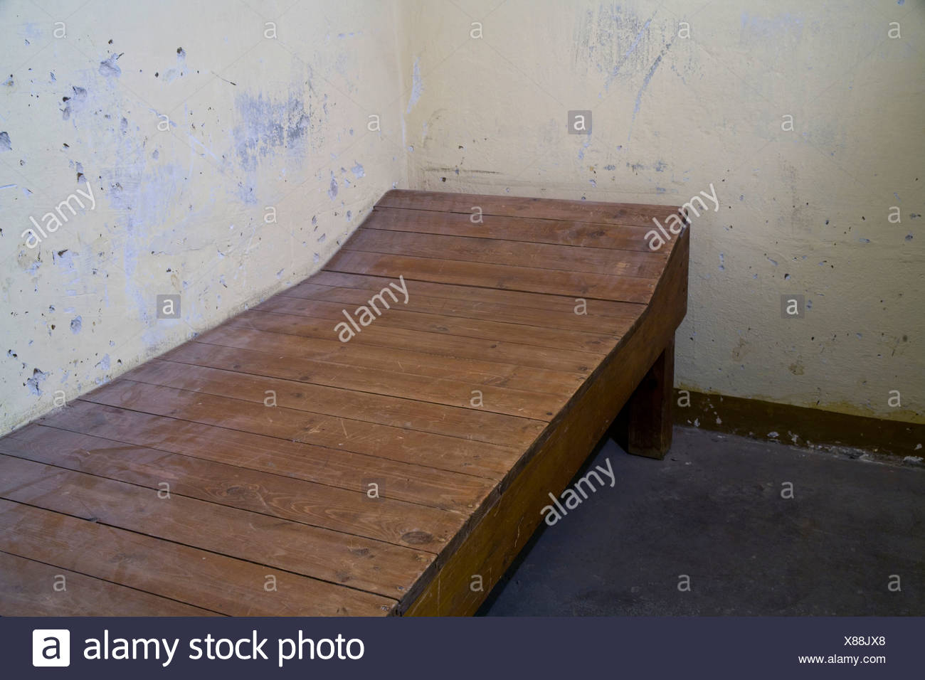 Cot in a windowless cell for solitary confinement, Berlin-Hohenschoenhausen memorial, former prison of the GDR's secret service - Stock Image