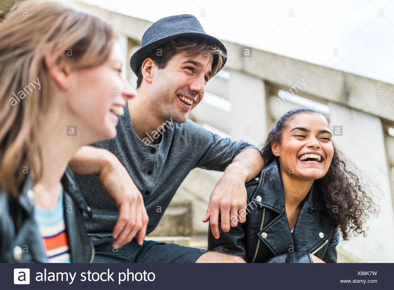 Three young adult friends on stairway chatting in Battersea Park - Stock Image