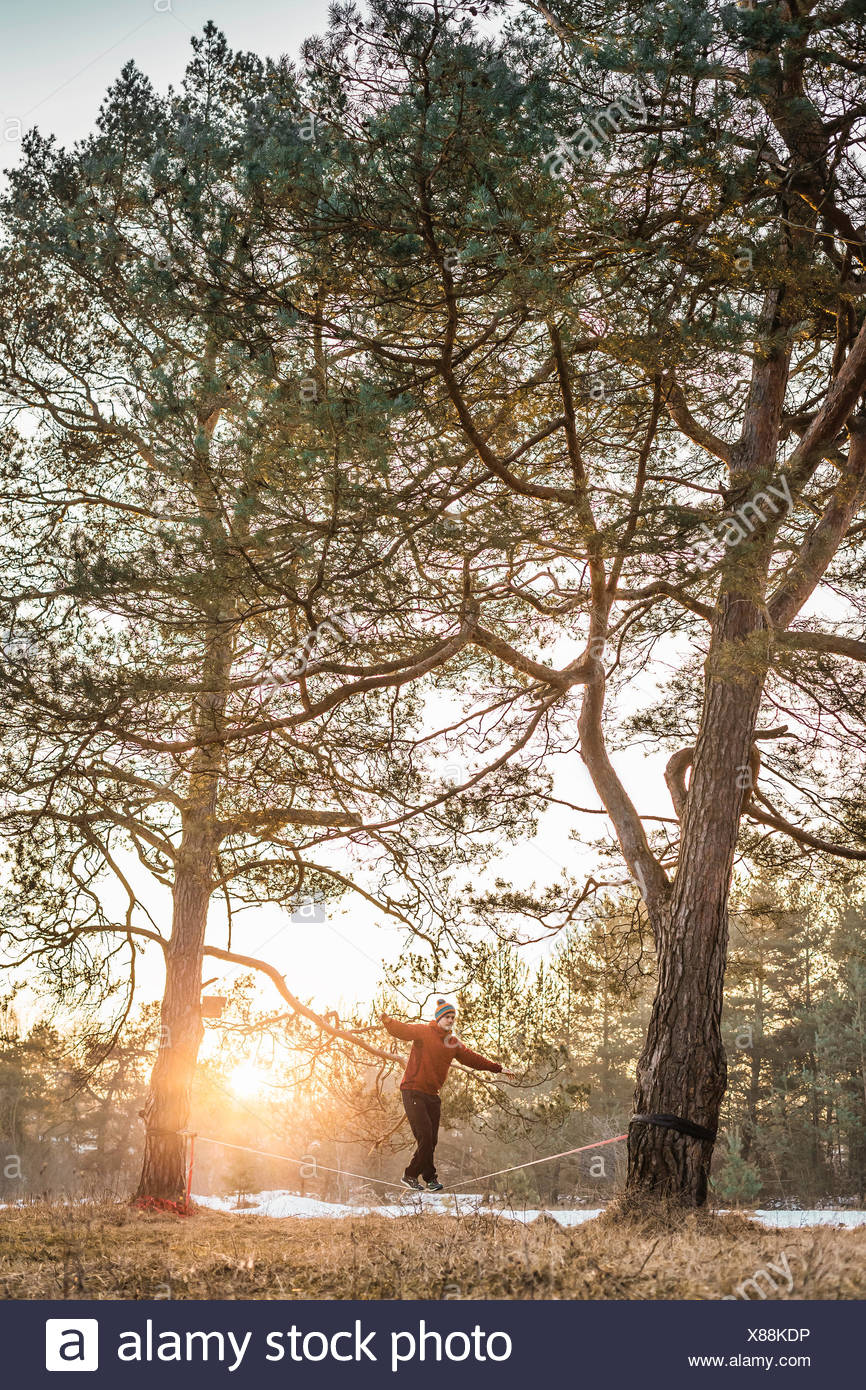 Young man balancing on slackline in lakeside forest - Stock Image