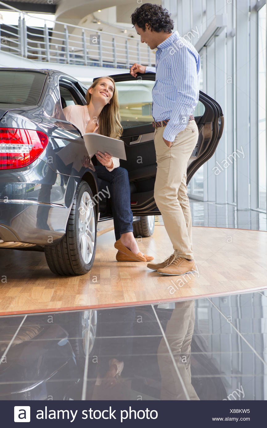 Couple looking at brochure in car dealership showroom - Stock Image