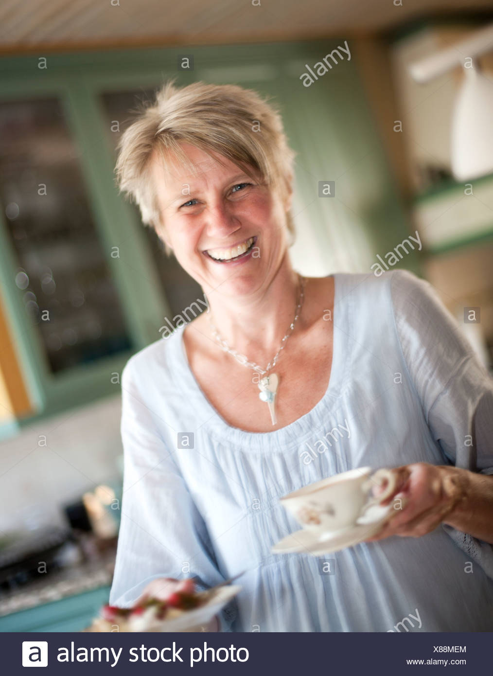 Portrait of woman carrying tea cups and smiling - Stock Image