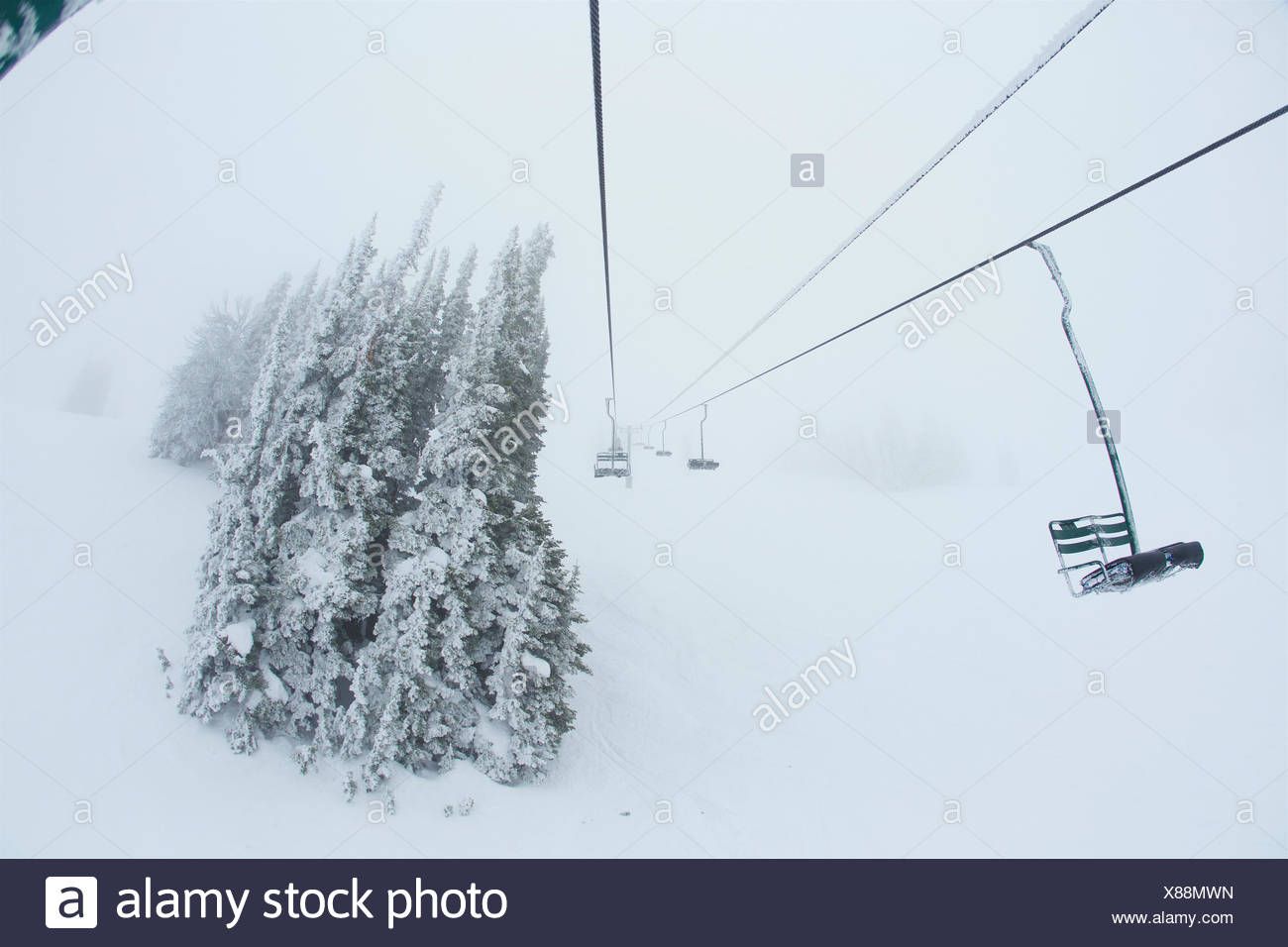 Rime covered chairlift in stormy whiteout conditions. - Stock Image