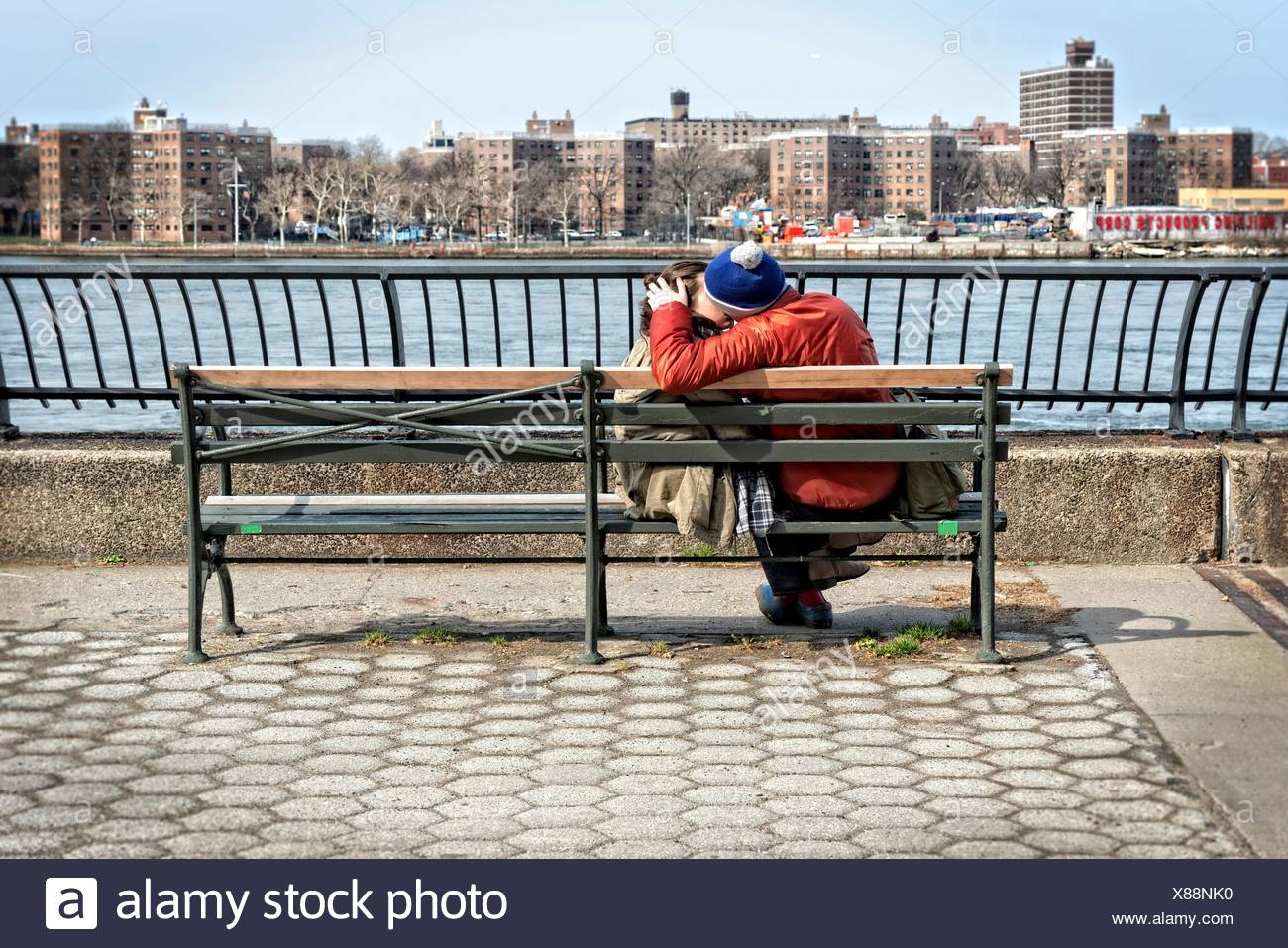 Young man and woman couple (20´s to 30´s), lovingly kissing on a river promenade bench. Stock Photo
