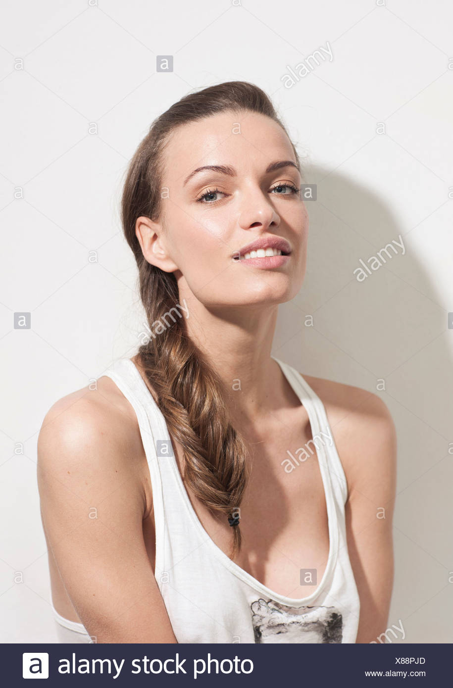 Young woman wearing vest and smiling, portrait - Stock Image