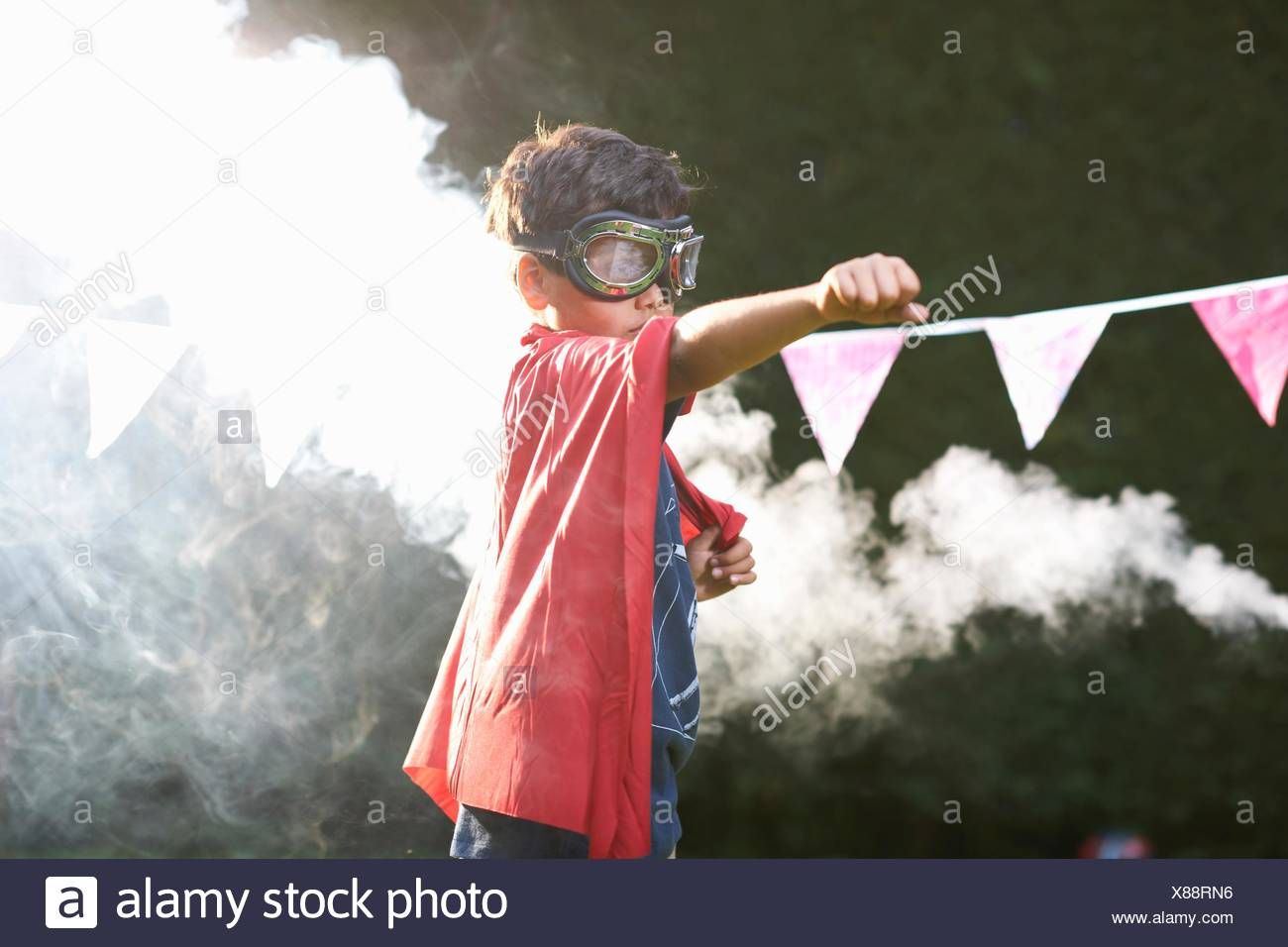 Boy wearing goggles and cape in superhero stance in front of smoke cloud - Stock Image