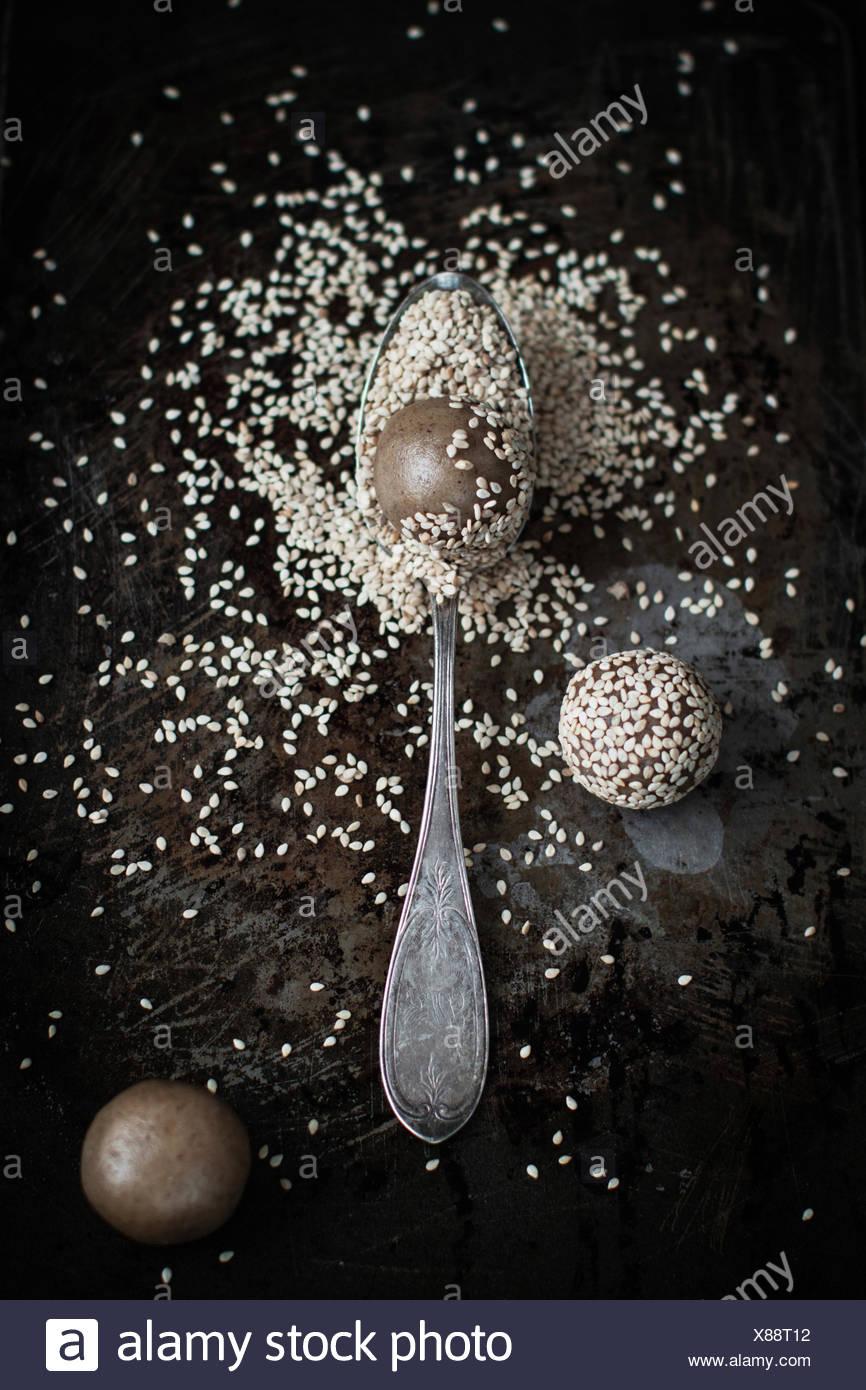 Work in progress for tahini cookies: sprinkling cookies with sesame seeds - Stock Image