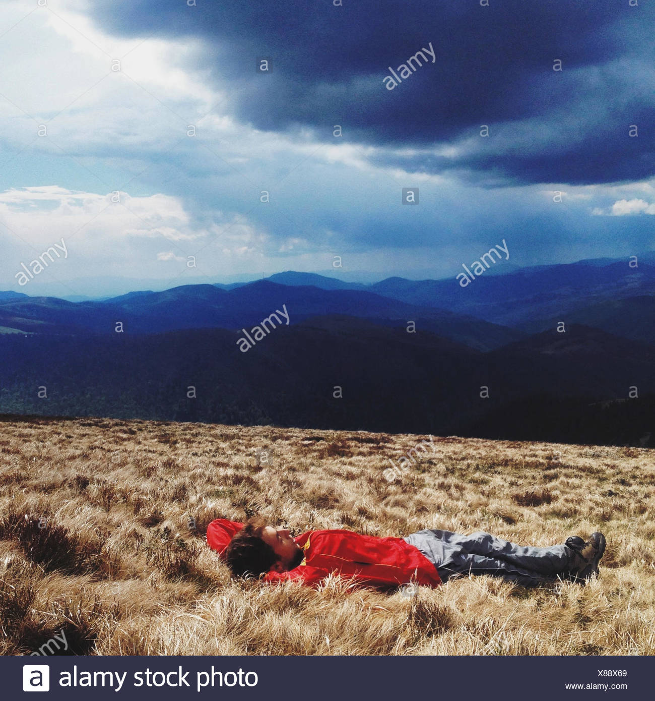 Man lying in grass in remote landscape - Stock Image