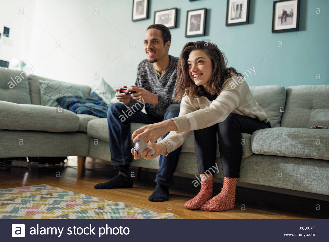 Sweden, Young couple playing video games in living room - Stock Image