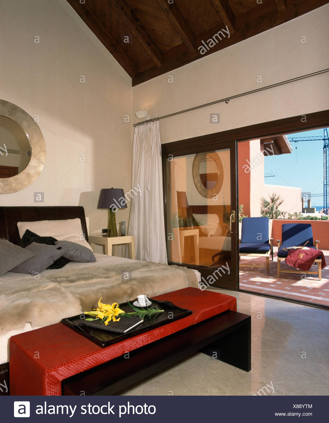 Red stool below bed with faux fur throw in modern Spanish bedroom with open glass doors to patio - Stock Image