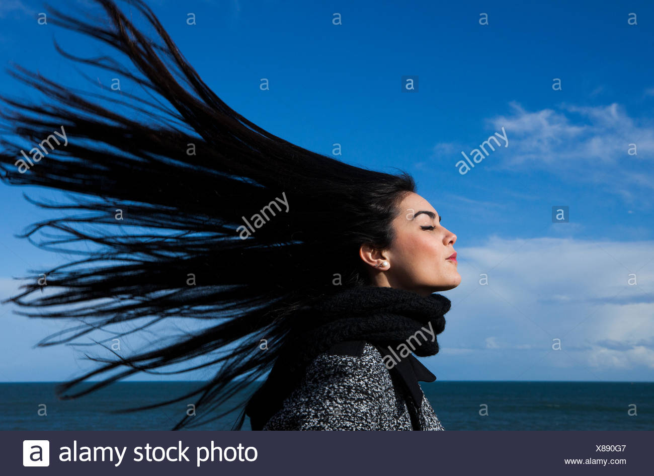 Young woman with hair blowing in the wind - Stock Image