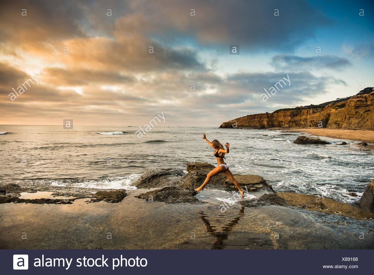 Young woman in bikini leaping from rocks on beach - Stock Image