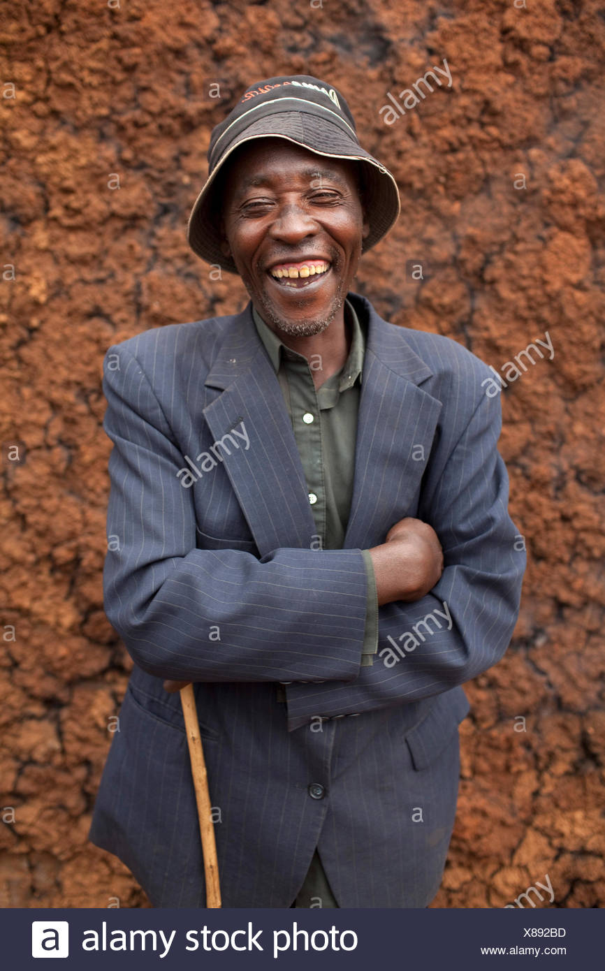 laughing man with hat and crook standing in front of a mud wall, portrait, Burundi, Karuzi, Buhiga - Stock Image