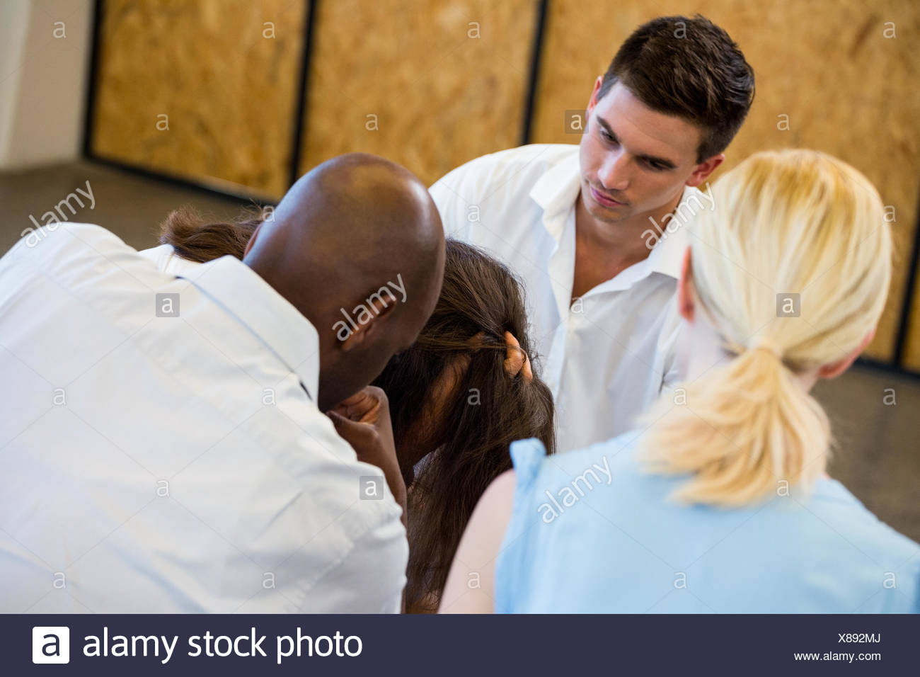 Colleagues comforting a unhappy woman - Stock Image