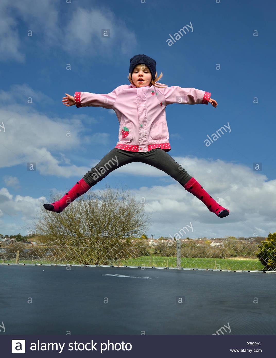 Preschool girl (2-3) jumping on trampoline - Stock Image