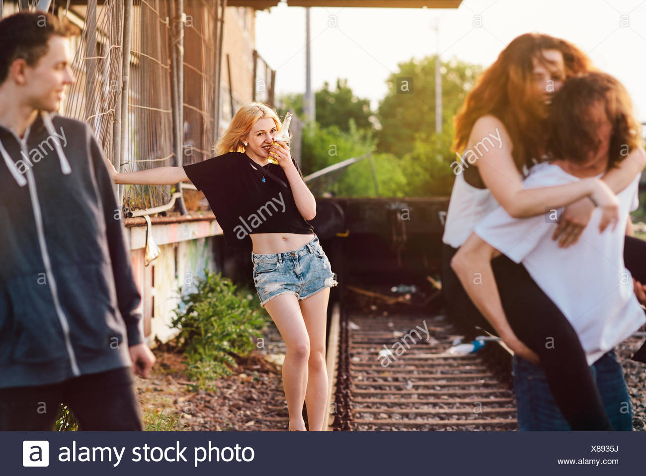 Friends romping around on tracks - Stock Image